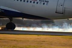 Aterrizaje de aeroplano de Delta Airlines en una pista con humo del neumático foto de archivo