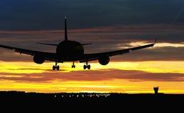 Aterrizaje de aeroplano en el cielo de la puesta del sol fotografía de archivo