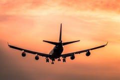 Aterrizaje de aeroplano en la puesta del sol fotos de archivo