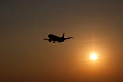 Aterrizaje de aeroplano en la puesta del sol Imagen de archivo libre de regalías