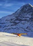 Aterrizaje de aeroplano rojo amarillo en el campo de aviación de la montaña en al suizo Imagen de archivo