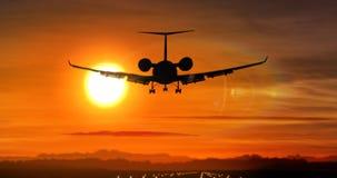 Aterrizaje de aeroplano - silueta del jet privado en puesta del sol imagenes de archivo