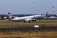 Aterrizaje de aviones de Austrian Airlines Embraer ERJ-195LR en la pista Fotografía de archivo libre de regalías