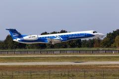 Aterrizaje de aviones de Dniproavia Embraer ERJ-145 en la pista Fotografía de archivo libre de regalías