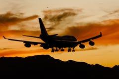 Aterrizaje de aviones en la puesta del sol Fotografía de archivo libre de regalías