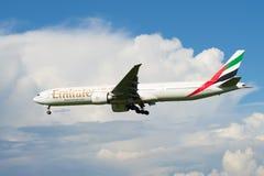 Aterrizaje de la línea aérea de los emiratos de Boeing 777-300 (A6-EGU) en un cielo nublado Imagen de archivo libre de regalías