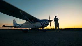 Aterrizaje de la pista con un aviador de sexo masculino y sus pequeños aviones durante puesta del sol almacen de metraje de vídeo