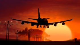 Aterrizaje de la silueta del aeroplano en puesta del sol Imagen de archivo