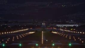 Aterrizaje del avión de pasajeros en la pista en la noche - visión trasera almacen de video