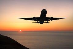 Aterrizaje del avión de pasajeros en la salida del sol Fotografía de archivo