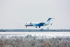 Aterrizaje del avión privado en el aeropuerto del invierno Imagenes de archivo
