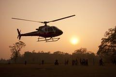 Aterrizaje del helicóptero en la puesta del sol, Nepal Foto de archivo