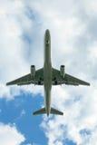 Aterrizaje del jet con las nubes Imágenes de archivo libres de regalías