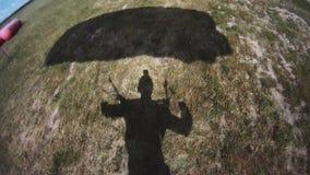 Aterrizaje profesional del paracaidista en campo verde Día asoleado Manía extrema almacen de metraje de vídeo