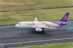 Aterrizaje tailandés del avión de la vía aérea de la sonrisa en el aeropuerto de Phuket Fotografía de archivo libre de regalías