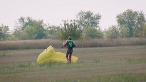 Aterrizan al paracaidista en campo y la baja de su paracaídas en la tierra después de vuelo, en día de verano almacen de video