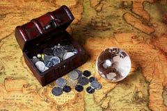 Atesore la caja, las monedas y el globo en fondo antiguo del mapa Fotografía de archivo