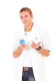 Atful fake doctor holding enema beckon to patient. Cute young doctor man fashionable looks in a uniform stock images
