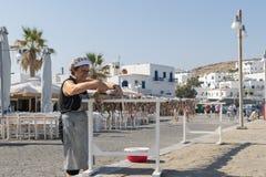 Athènes, Grèce le 15 août 2015 Vieille dame accrochant un poulpe pour sécher au soleil à l'île de Paros en Grèce photo stock