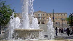 Ath?nes, Gr?ce - 26 04 2019 : Place de syntagme avec une fontaine, des touristes et une vue du Parlement grec le jour ensoleillé clips vidéos