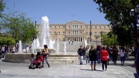 Ath?nes, Gr?ce - 26 04 2019 : Place de syntagme avec une fontaine, des touristes et une vue du Parlement grec le jour ensoleillé banque de vidéos