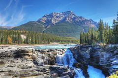 Athabasca Falls with Rocky Mountain peak behind Stock Image