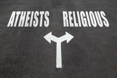 Atheists vs religious choice concept. Two direction arrows on asphalt Stock Images