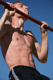 Atheletic exercise. The Young man executes the atheletic exercise on horizontal bar Stock Images