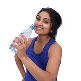 Athelte femminile sorridente con la bottiglia di acqua Immagine Stock