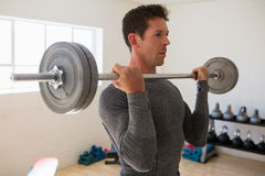 Athelte lifting barbell at gym Stock Images