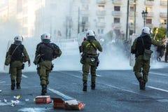 ATHEN - Bereitschaftspolizei mit ihrem Schild, gehen während einer Sammlung vor der Athen-Universität in Deckung Lizenzfreie Stockbilder