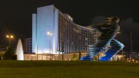 Athen, Griechenland am 25. November 2015 Athen bis zum Nacht gegen die Läuferstatue und ein modernes Gebäude stockfoto