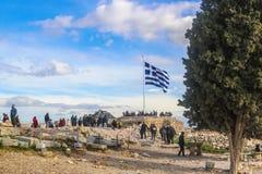 2018_01_03 Athen Griechenland - Touristen zur Akropolise in Athen-Versammlung um die griechische Flagge, die Fotos mit der Kapell stockbild