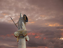 Athena statue, the goddess of wisdom and philosophy. Under a fiery sky royalty free stock image