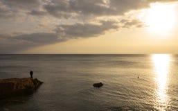 Athene/Griekenland: Een eenzame mens die op de zonsondergang op de kust letten dichtbij Athene, Griekenland royalty-vrije stock fotografie