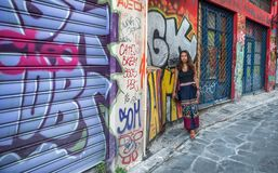 Athens, Greece-August 17, 2018: Asian woman leaning against wall surrounded by graffiti stock photos