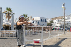 Athens, Greece 15 August 2015. Old lady hanging an octopus to dry in the sun at Paros island in Greece. Stock Photo