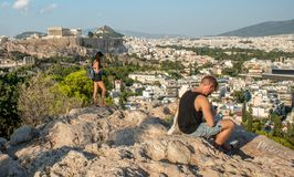 Athens Greece/August 17, 2018: Young male and girl on mobile phones in front of Acropolis stock photos