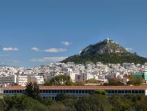 Athens, Greece on a brilliant clear day. Lykavittos hill surrounded by the city of Athens on a brilliant clear afternoon Royalty Free Stock Image