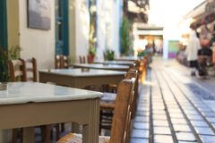 Athens, Greece. Greek tavern tables and chairs in a row. Athens, Greece. Greek tavern empty tables and chairs in a row, blur pedestrian and market background Stock Photos