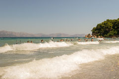 Athens, Greece 19 July 2015. Big waves on a beach with people playing and enjoying there free time. Stock Image
