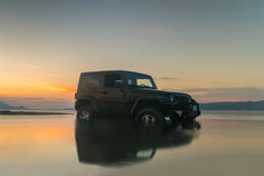 Athens, Greece 1 July 2016. Jeep 4x4 in the mud against a beautiful sunset. Royalty Free Stock Images