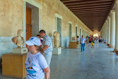 ATHENS, GREECE - JUNE 08, 2009: Tourists showing greek sculpture Stock Image