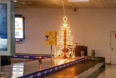 Lighted airplane Christmas tree on luggage conveyer belt at almost deserted airport late at night at Ch stock photography
