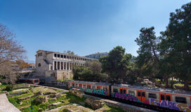Athens, Greece - March 4, 2017:  View of Stoa of Attalos. Building with Acropolis in the background and overground trains in the foreground Royalty Free Stock Photos