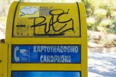 Close up shot of an old outdoors Greek yellow card phone Royalty Free Stock Photography