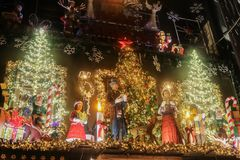 Ornate lit up Christmas display at night above Little Kooks store downtown with trees and carolers royalty free stock images