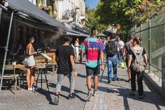 ATHENS, GREECE - SEPTEMBER 17, 2018: Tourists walk crowded path past cafes and souvenir shops in Monastiraki, Athens stock image