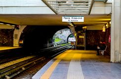 Woman waiting at outdoor covered metro station in early morning with a train approaching royalty free stock images