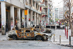 Athens Street After Riots. ATHENS (GREECE) - December 15: Burnt cars and garbage containers placed as a barricade by rioters in an Athens downtown street during Royalty Free Stock Image